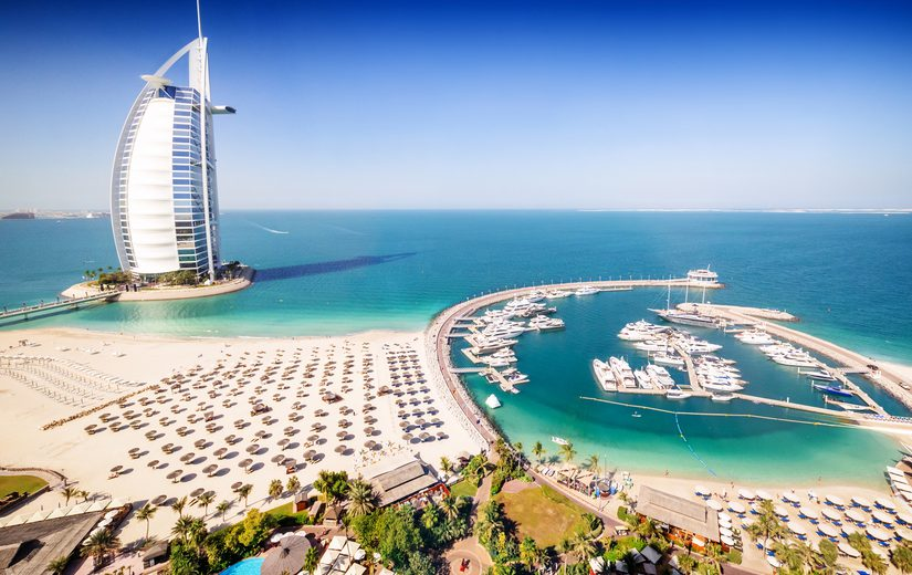 Dubai, United Arab Emirates - December 10, 2014: The Burj Al Arab Hotel, left side on the beach near Madinat Jumeriah Resort. The Burj Al Arab is a luxury hotel located in Dubai, United Arab Emirates. At 321 m (1,053 ft), it is the fourth tallest hotel in the world. The Burj Al Arab stands on an artificial island 280 m (920 ft) out from Jumeirah beach, and is connected to the mainland by a private curving bridge. It is an iconic structure whose shape mimics the sail of a ship.